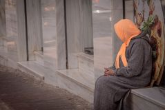 Une femme agée avec la séance principale couverte image libre de droits