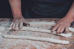 Une femme agée déroule d'une pâte lisse crue pour faire sur cuire au four un fond foncé photos libres de droits