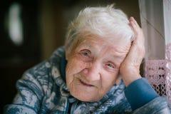 Une femme agée dans la maison se reposant à la table regardant la fenêtre Photographie stock libre de droits