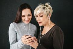 Une femme agée et une jeune fille écoutent la musique ensemble Communication entre les personnes de différentes générations Images stock