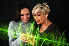 Une femme agée et une jeune fille écoutent la musique ensemble Communication entre les personnes de différentes générations Image stock