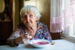 Une femme agée mangeant de la soupe se reposant à une table images stock