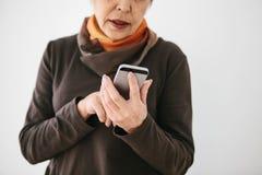Une femme agée moderne positive tient un téléphone portable et l'emploie La génération plus ancienne et la technologie moderne Image libre de droits