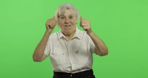 Une femme agée montre la stupéfaction, la joie et les sourires Vieux grand-m?re Plan rapproch? clips vidéos