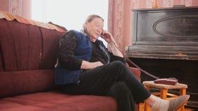 Une femme agée parle le téléphone à la maison Image libre de droits