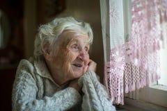 Une femme agée repose et regarde la fenêtre photographie stock