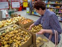 Une femme agée sélectionne des pommes de terre dans un paquet Photo stock