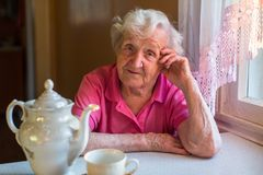 Une femme agée s'asseyant à la table dans la cuisine Photos stock