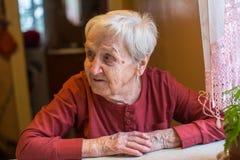 Une femme agée s'asseyant à la table dans la maison Photographie stock