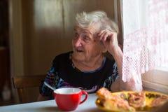 Une femme agée s'asseyant au thé potable de table avec des tartes Photo stock