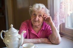 Une femme agée s'asseyant dans la cuisine Portrait Image stock