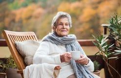 Une femme agée s'asseyant dehors sur une terrasse dedans un jour ensoleillé en automne images stock