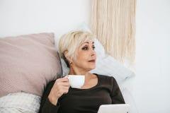 Une femme agée se situant en café potable de matin de lit utilise un comprimé pour regarder des actualités ou pour causer avec de Image stock
