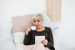 Une femme agée se situant en café potable de matin de lit utilise un comprimé pour regarder des actualités ou pour causer avec de Photos stock