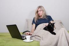 Une femme agée seule en verres s'assied sur un sofa sous une couverture avec un ordinateur portable et un chat noir Image stock
