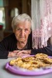 Une femme agée repose à une table avec les pâtisseries rustiques heureux Photo stock