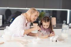 Une femme aide une fille avec un biscuit fait maison La fille observe la cuisson de femme Photos stock