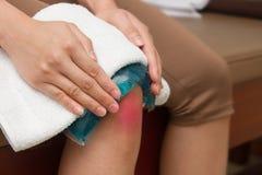 Une femme appliquant l'emballage froid sur le genou blessant gonflé après accid Photos stock