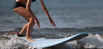 Une femme apprend à surfer sur la vague images stock