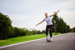 Une femme apprennent comment monter un monocycle Elle essaye de garder son équilibre Images libres de droits