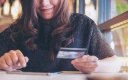 Une femme asiatique de visage souriant tenant la carte de crédit et à l'aide du PC de comprimé dans le restaurant photographie stock libre de droits