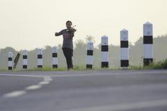 Une femme asiatique joue le violon du côté de route Photo stock