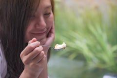 Une femme asiatique ont plaisir à manger et tenir le gâteau avec la cuillère en café Photos stock
