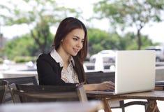Une femme assez asiatique d'affaires à l'aide de l'ordinateur portable extérieur photo libre de droits