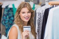Une femme assez blonde montrant ses cartes de crédit Photos stock