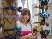 Une femme attirante dans des lunettes de soleil des achats de boutique, accessoires pour des femmes sur un fond clair brouillé Image stock