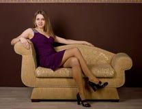 Une femme attirante s'asseyant sur le sofa photographie stock libre de droits