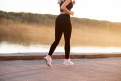 Une femme avec une figure mince et musculaire court autour dans les vêtements noirs de sports et des espadrilles blanches en natu image stock