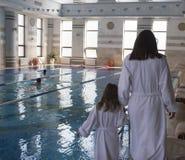 Une femme avec une fille dans des peignoirs blancs autour de la piscine image stock