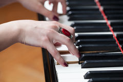 Une femme avec l'anneau rouge jouant le piano Images libres de droits