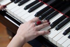 Une femme avec l'anneau rouge jouant le piano Images stock