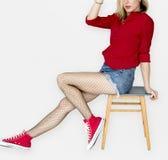 Une femme avec l'espadrille rouge se reposant sur une chaise Photos stock