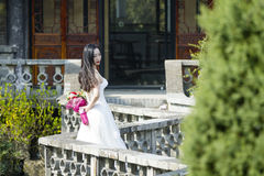 Une femme avec la robe de mariage blanche portent le support nuptiale de bouquet dans un cloître en parc de la BO de shui de Chan Image stock