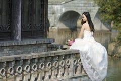 Une femme avec la robe de mariage blanche portent le support nuptiale de bouquet dans un cloître en parc de la BO de shui de Chan Images libres de droits