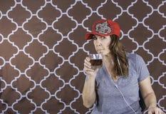 Une femme avec le chapeau rouge prenant une boisson Images stock