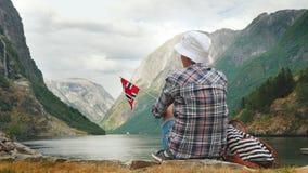 Une femme avec le drapeau de la Norvège dans sa main admire le beau fjord Tourisme dans le concept de la Scandinavie photos stock