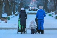 Une femme avec une poussette dans la ville à l'hiver Photos stock