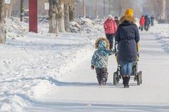 Une femme avec une poussette dans la ville pendant l'hiver La maman marche avec un enfant pendant l'hiver Photos stock