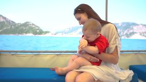 Une femme avec son petit fils est sur le bateau, le bébé esquive l'eau de la mer banque de vidéos