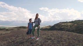 Une femme avec un enfant admirant la vue des montagnes famille des touristes avec des sacs à dos la maman et la petite fille sont clips vidéos
