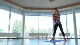 Une femme avec un enfant dans des ses bras s'exerce en gymnastique, dans une salle de yoga un jour d'été, mouvement lent clips vidéos