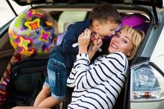Une femme avec un enfant dans la voiture Photo stock