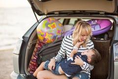 Une femme avec un enfant dans la voiture Images stock
