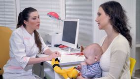Une femme avec un enfant en bas âge consulte un pédiatre clips vidéos