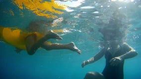 Une femme avec un enfant nage dans le tir sous-marin d'eau de mer banque de vidéos