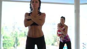 Une femme avec un enfant répète des exercices de sports après un entraîneur de femme clips vidéos